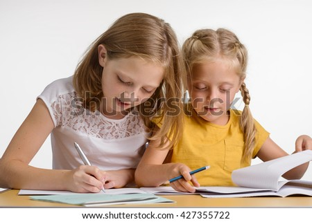 Very important process of the development of children. Two young girls are busy with their homework and preparation for lessons. Family support between siblings.
