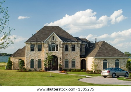 Very large and beautiful stone and brick house on a small lake with generic car in front circle drive and white puffy clouds in the sky. - stock photo