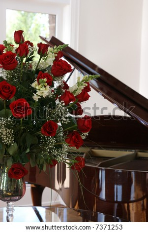 very large beautiful boquet of roses on a table in front of a grand piano