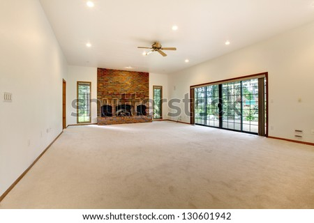 Very large empty living room with brick fireplace and sliding doors to the back yard. - stock photo