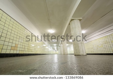 Very long corridor with yellow tiles on walls, granite floors and columns.