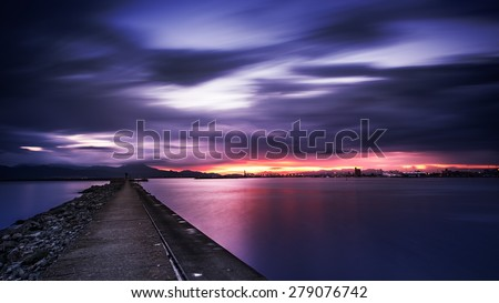 Very long exposure of cloudy sumset in the port - It was given an purposely dramatic effect and dark to make the photo more interesting - stock photo