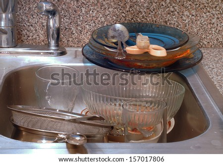 Very messy kitchen with piles of dirty dishes  - stock photo