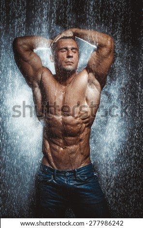 very muscular handsome athletic man in the rain - stock photo