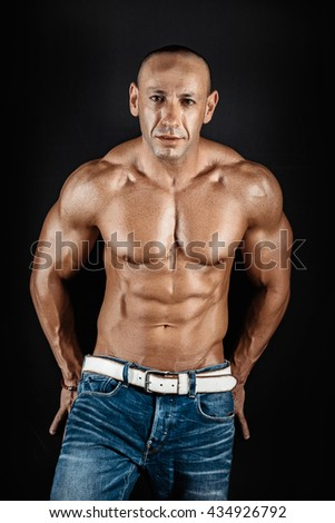 very muscular handsome athletic man on black background - stock photo