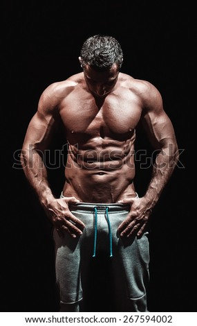 very muscular handsome athletic man on black background, naked torso - stock photo
