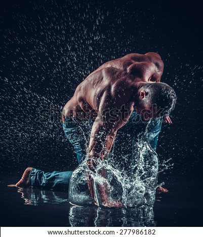 very muscular handsome athletic man striking with a hand on water - stock photo
