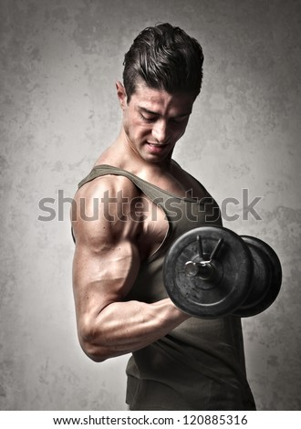 Very muscular man lifting a dumbbell with his right arm - stock photo