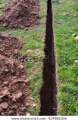 very narrow trench in summer farm yard through grass  for water pipe - stock photo