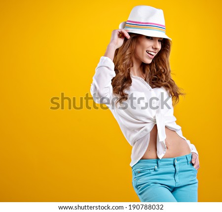very nice and sexy spring  brunette girl with hat in a yellow background