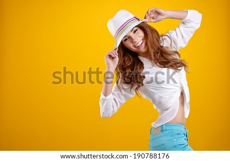 very nice and sexy spring  brunette girl with hat in a yellow background  - stock photo