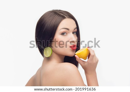 Very nice dark-haired woman with extraordinary earrings and one lemon in her hand, giving us wonderful kiss. Isolated on the white background