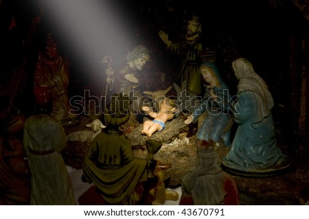 Very old ceramic nativity display with light shinning down on Christ child - stock photo