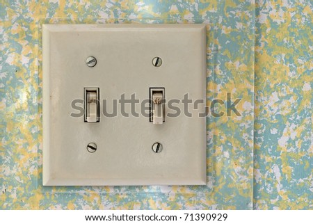 Very old double wall switch with clear plastic cover against a colorful wall. - stock photo
