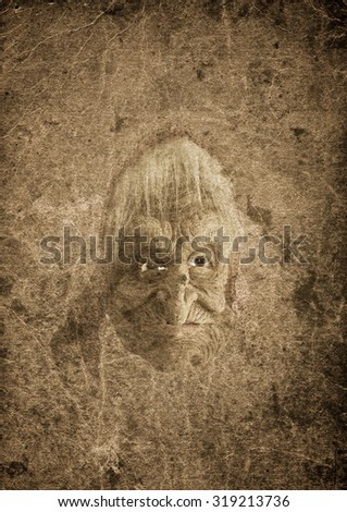 Very old grunge paper background with a witch, crafted head doll - stock photo