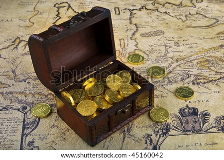 Very old map with treasure chest full of golden coins on a vintage map - stock photo