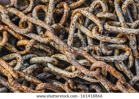 Very old, obsolete, weathered, badly corroded, heap of rusty chain links, covered with layers of decomposed metal crust and scales of rust peeling off. - stock photo