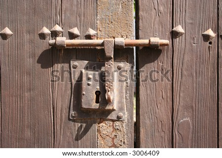 very old rusty lock on a wooden door to a courtyard garden in Teguise (Lanzarote) - stock photo