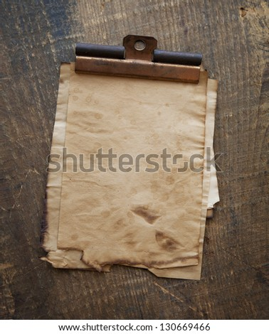Very old sheets of memo paper with vintage copper clip, on old wood surface. - stock photo