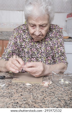 very old woman peeling garlic in kitchen - stock photo