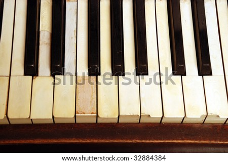 very old wooden piano with ivory keys broken and scratched - stock photo