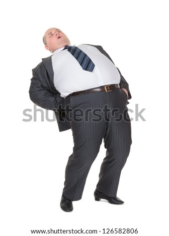 Very overweight man in a stylish suit and tie with acute back ache bending over backwards to alleviate the pain with an agonised expression on his face isolated on white - stock photo