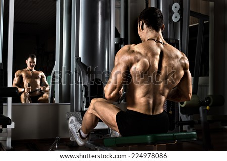 very power athletic guy bodybuilder,  execute exercise with gym apparatus, on broadest muscle of back - stock photo