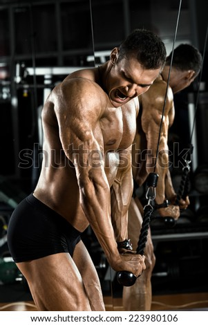 very power athletic guy bodybuilder,  execute exercise with gym apparatus, on triceps - stock photo