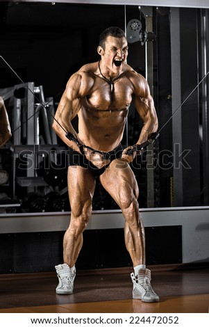 very power athletic guy bodybuilder,  execute exercise with gym crossover apparatus, on pectoral muscle - stock photo