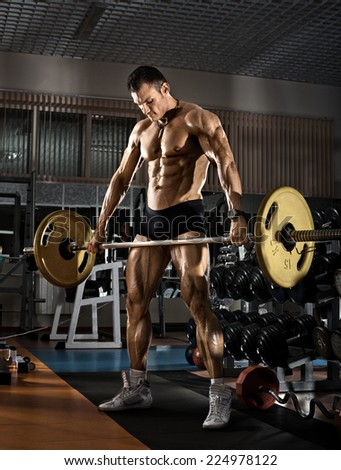 very power athletic guy bodybuilder,  execute exercise with  weight , in the standing position - stock photo