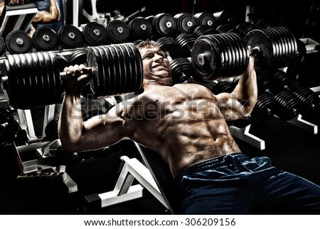 very power athletic guy ,  execute exercise press with  dumbbells, in gym - stock photo