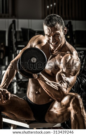very power athletic guy ,  execute exercise with  dumbbells, on black background - stock photo