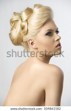 very pretty blonde woman with elegance hair style, she is turned in profile at right and she looks up in front of her - stock photo