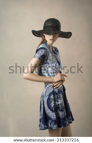 very pretty brunette model wearing summer black hat and lovely blue printed top and skirt, in fashion pose covering her eyes with hat