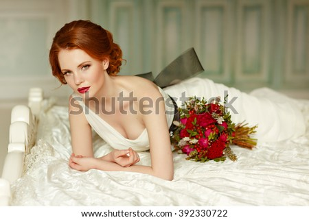 Very pretty sophisticated red-haired girl with a bouquet in his hand lying on the bed, in the interiors of the studio