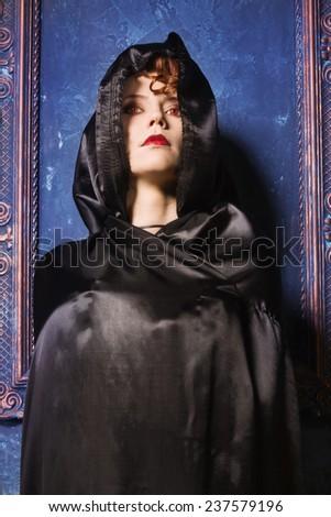 Very pretty woman vamp praying in the darkness - stock photo