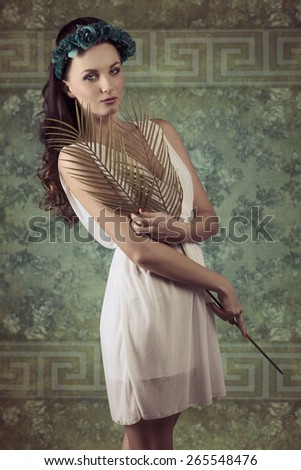 very pretty woman with long brown wavy hair posing in romantic spring portrait with flowers on head, white dress  and palm leafs in the hand - stock photo
