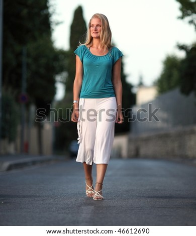 Very pretty young woman walking on the road