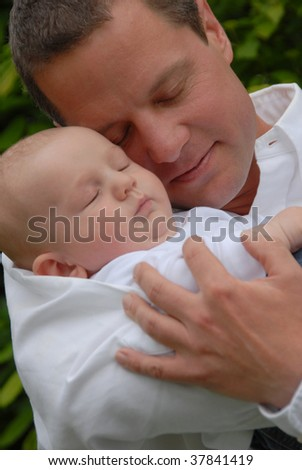 Very proud and happy young father holding his baby