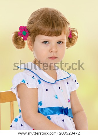 Very quiet little girl sitting on a chair.kindergarten, the concept of childhood and joy, teens - stock photo