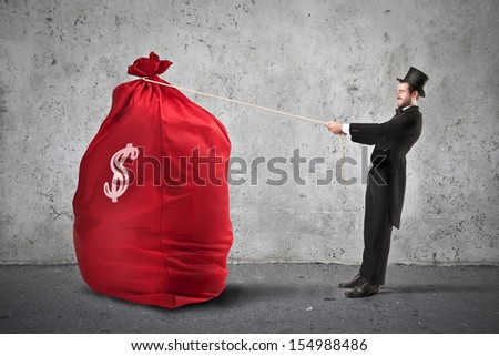very rich businessman pulls big sack of money - stock photo