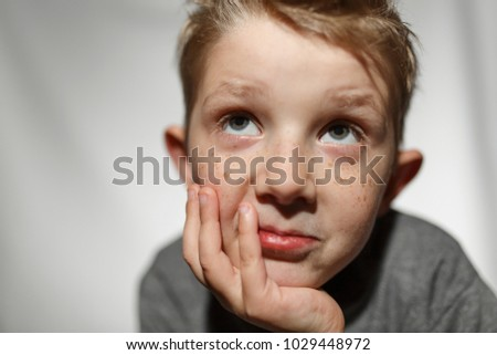 very sad little boy, the child is sad on a white background in the studio