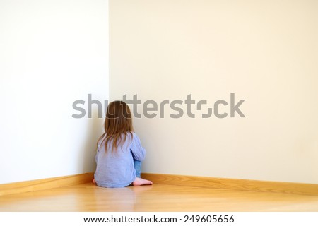 Very sad little girl sitting on a floor at home - stock photo