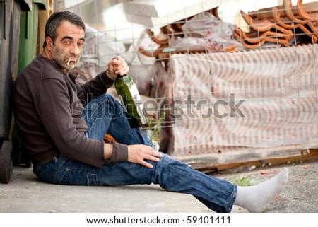 very sad man drinking wine on sidewalk near trashcan - stock photo