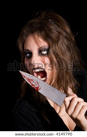 Very scary woman about to lick the blood of her knife - stock photo