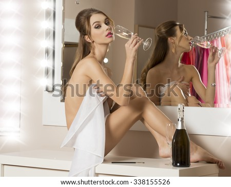 very sensual brunette woman sitting in bathroom near mirror and drinking champagne. Wearing only white towel on her naked body. Preparing and make-up for the new year party night  - stock photo