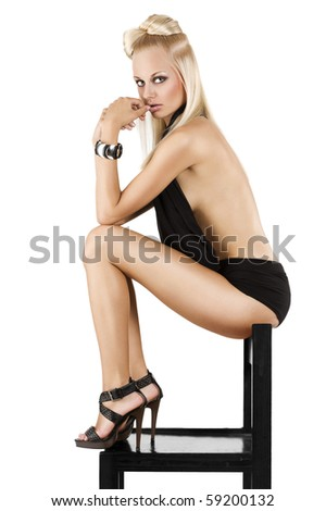 very sensual girl in hot panty and black material sitting on a chair looking in camera - stock photo