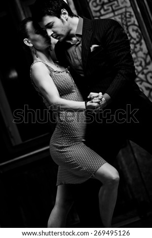 Very sensual pose of a couple performing a lover's dance: tango. Black and white image with grain film added as effect. - stock photo