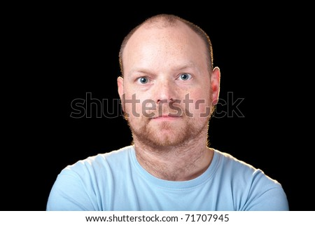very serious male in blue shirt isolated on black background - stock photo