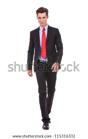 very serious young man walking forward to the camera onwhite background - stock photo